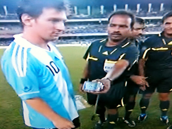 Indian Assistant Referee handing camera to Messi